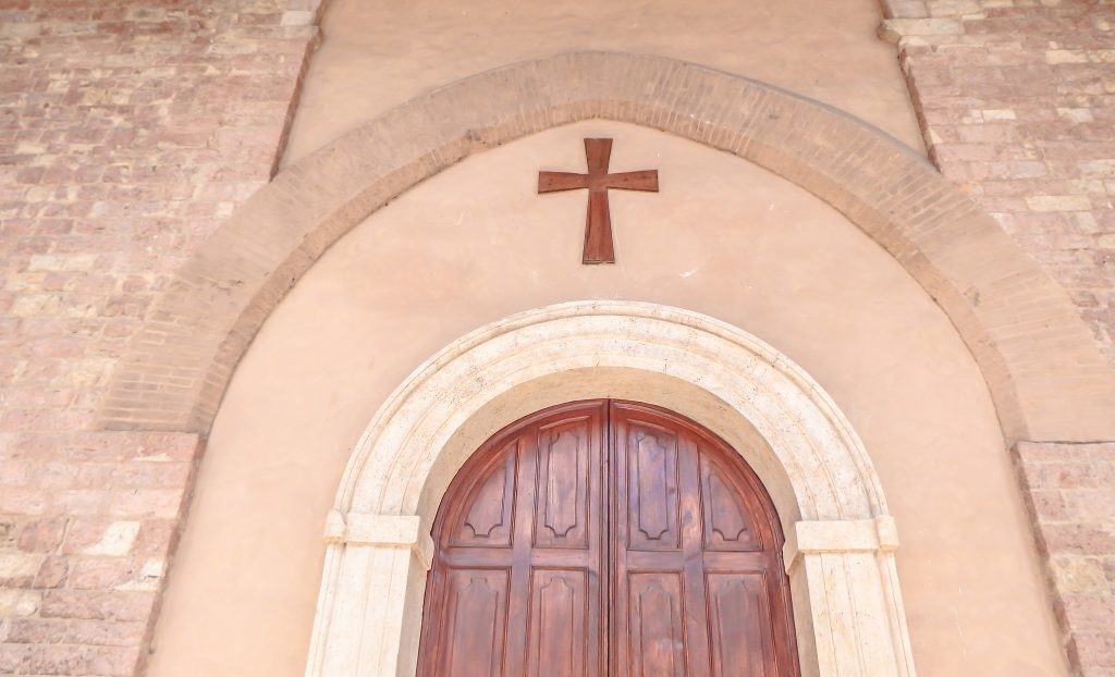 A cross over the door of Temple Minerva // Day trip to Assisi, Italy